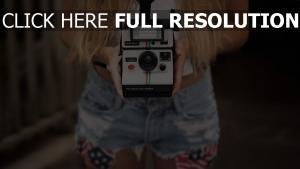 polaroid kamera hände jeans mädchen